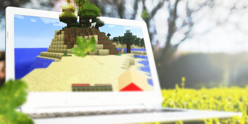 Laptop uzyskany za pomocą wynajmu laptopów gamingowych. Na wyświetlaczu widać grę, w tle widać naturę.